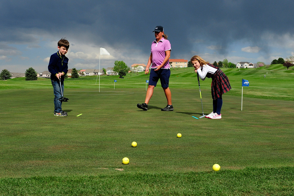 Description of . DENVER, CO - MAY 7: Eva Hellvig, 7, right, watches as Cameron Fay, 6, hits a golf ball during their first class with Nina Krats, center, at Foothills Golf Course on May 7, 2014, in Denver, Colorado. Foothills Park and Recreation is aiming to increase participation in its golf programs, especially in regards to youth involvement. (Photo by Anya Semenoff/The Denver Post)