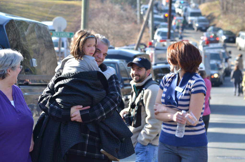 Description of . Families gather on the road leading to Sandy Hook Elementary School in Newtown. Melanie Stengel/Register