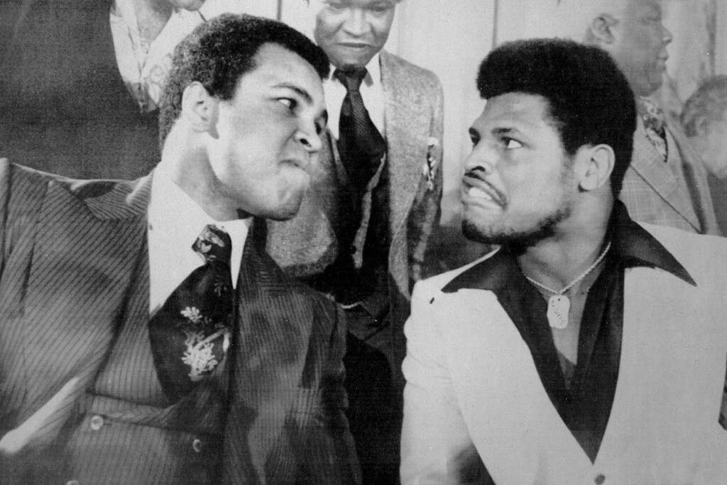 Description of . Hyping Next Title Defense -- Muhammad Ali, the world heavyweight champion, left, strains to stare down a grimacing Leon Spinks, the Olympic heavyweight champion, during a news conference Thursday to promote their Feb. 15 title bout in Las Vegas. It was announced Thursday that Ali has signed a $12 million contract to defend his championship next September against Ken Norton. 1977. Credit: AP Laserphoto