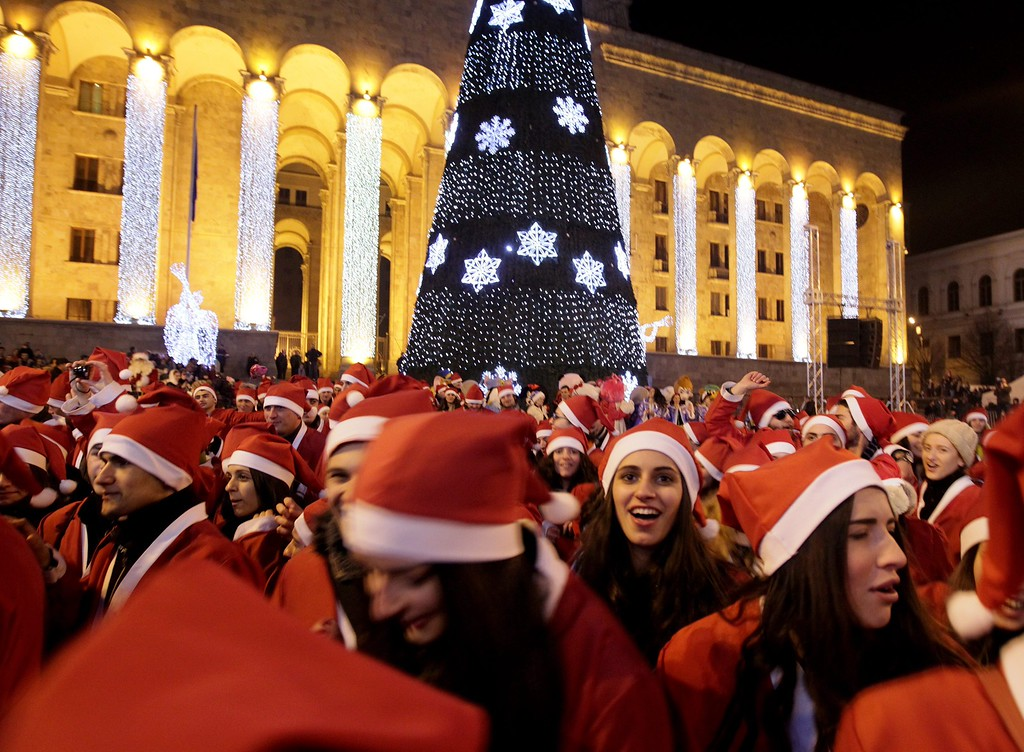 Description of . Georgian Santa Clauses greet children in front of the former Parliament building decorated with a Christmas tree in Tbilisi, Georgia, 25 December 2013.  EPA/ZURAB KURTSIKIDZE