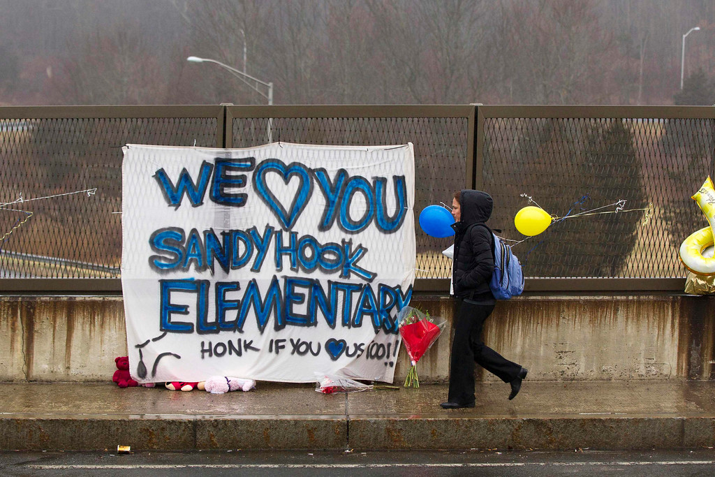 Description of . A woman walks over a freeway overpass near a memorial for the victims of the recent shooting in Sandy Hook Village in Newtown, Connecticut, December 16, 2012. Twelve girls, eight boys and six adult women were killed in a shooting on Friday at Sandy Hook Elementary School in Newtown.  REUTERS/Lucas Jackson