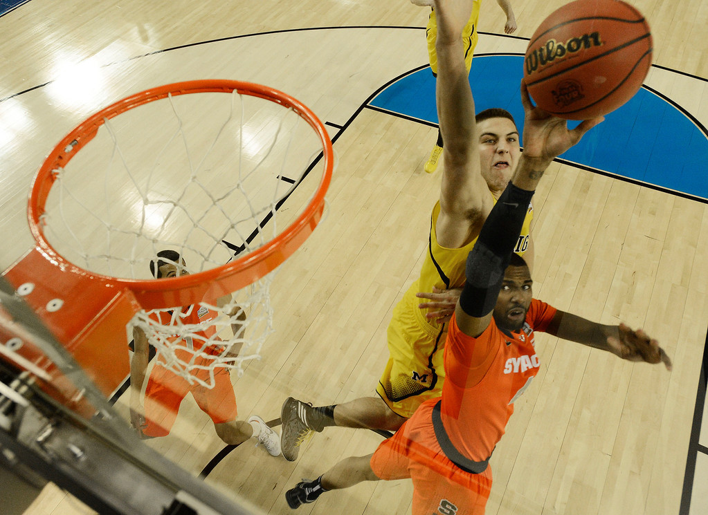 Description of . Syracuse's Nolan Hart (4) shoots against Michigan's Mitch McGary (4) during the first half of the NCAA Final Four tournament college basketball semifinal game Saturday, April 6, 2013, in Atlanta. (AP Photo/NCAA Photos, Chris Steppig, Pool)