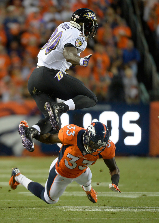 Description of . Baltimore Ravens running back Bernard Pierce (30) leaps over Denver Broncos safety Duke Ihenacho (33) in the first quarter.  (Photo by John Leyba/The Denver Post)