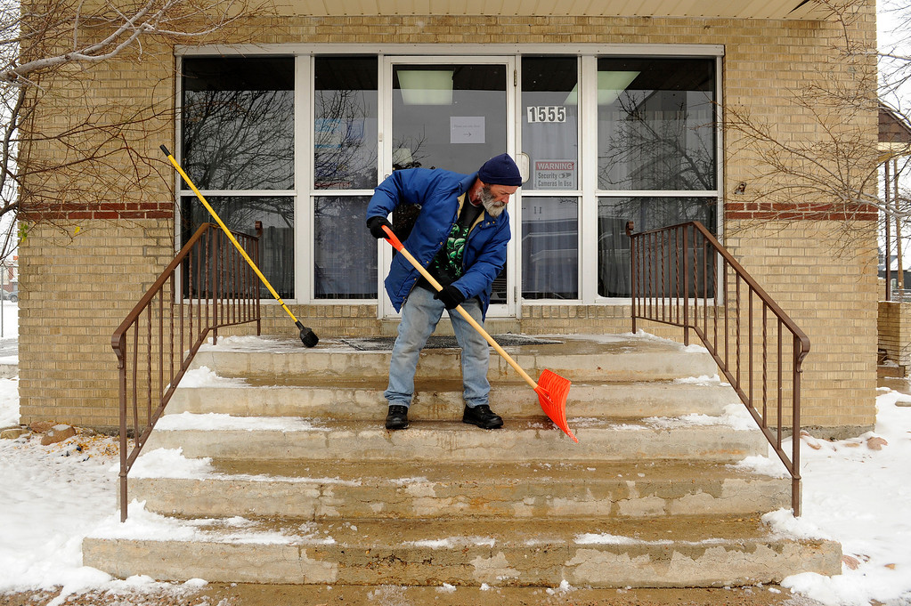 Description of . AURORA, CO - NOVEMBER 21: Virgil Barry clears ice from the steps at Aurora Warms the Night during a Cold Weather Shelter Program at the facility on November 21, 2013, in Aurora, Colorado. Barry used to receive assistance from the shelter program himself, but when he attained housing earlier this month, he decided to return to Aurora Warms the Night (AWTN) to volunteer. AWTN provides assistance to the homeless with a number of initiatives, including the Cold Weather Shelter Program which gives clients motel vouchers, food, clothing and hygiene kits on nights expected to be 20 degrees or colder. (Photo by Anya Semenoff/YourHub)