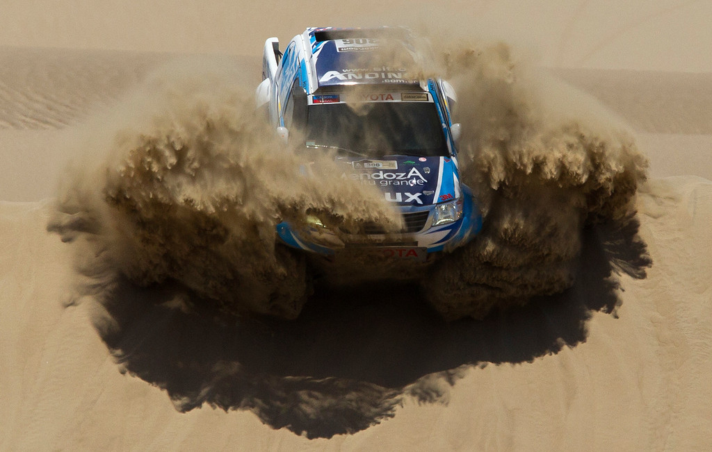 Description of . Totoya's Lucio Alvarez and co-driver Bernardo Graue of Argentina compete in the 1st stage of the 2013 Dakar Rally between Lima Pisco, Peru, Sunday, Jan. 6, 2013. The race finishes in Santiago, Chile, on Jan. 20. (AP Photo/Victor R. Caivano)