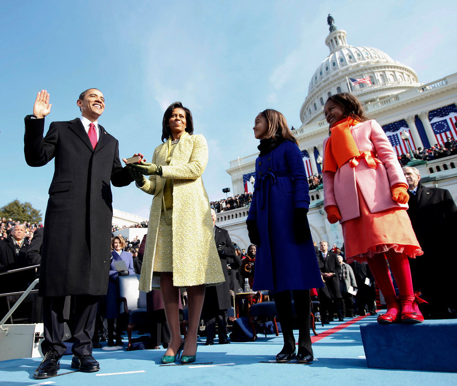Description of . FILE - This Jan. 20, 2009 file photo shows Barack Obama, left, taking the oath of office from Chief Justice John Roberts, not seen, as his wife Michelle, holds the Lincoln Bible and daughters Sasha, right and Malia, look on at the U.S. Capitol in Washington. Michelle Obama is wearing a yellow sheath and coat by Isabel Toledo. Michelle Obama has proven her fashion savvy time and time again since she was introduced to the country as first lady on Inauguration Day 2009. In the past four years she has adeptly walked the line between directional fashionista and everywoman. (AP Photo/Chuck Kennedy, Pool, file)