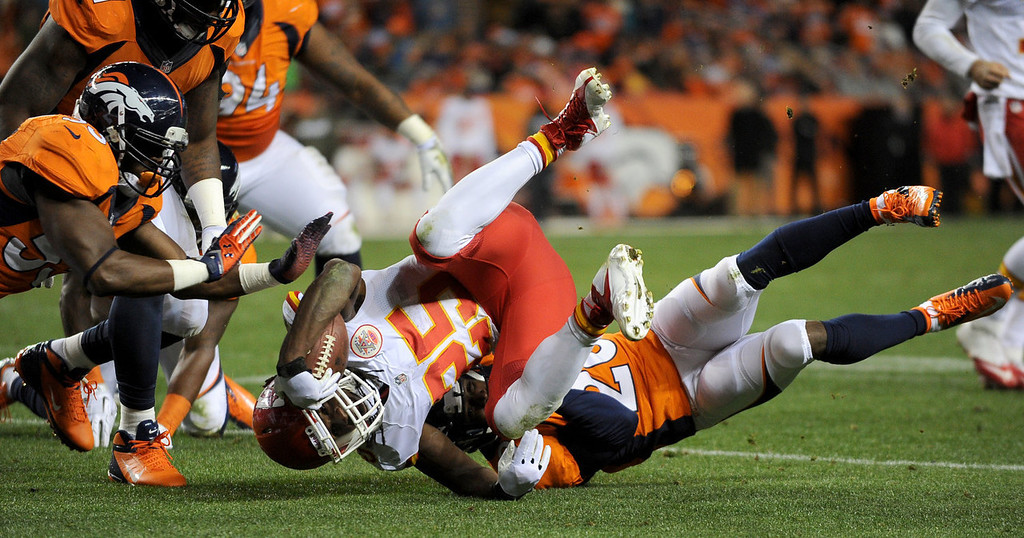 Description of . Kansas City Chiefs running back Jamaal Charles (25) is tackled by Denver Broncos strong safety Mike Adams (20) during the second quarter. The Denver Broncos vs. the Kansas City Chiefs at Sports Authority Field at Mile High in Denver on November 17, 2013. (Photo by Tim Rasmussen/The Denver Post)