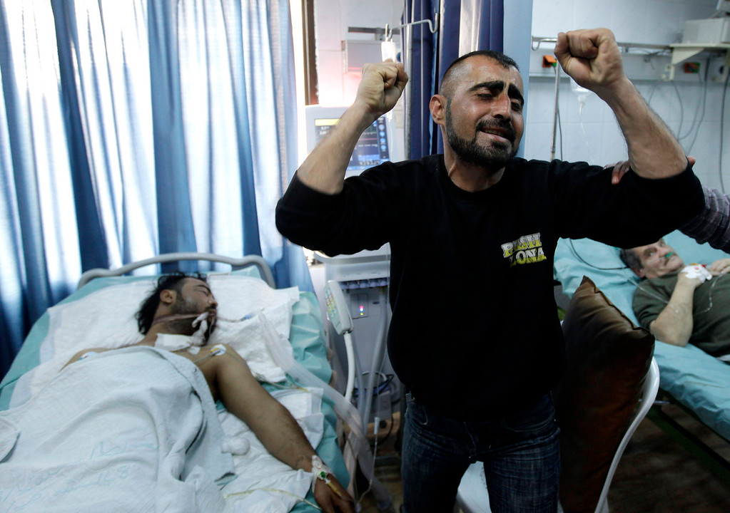 Description of . FILE - A Syrian man reacts next to his brother, who was seriously wounded during a violence between security forces and armed groups in Latakia, northwest of Damascus, Syria, on Sunday, March 27, 2011. (AP Photo/Hussein Malla, File)