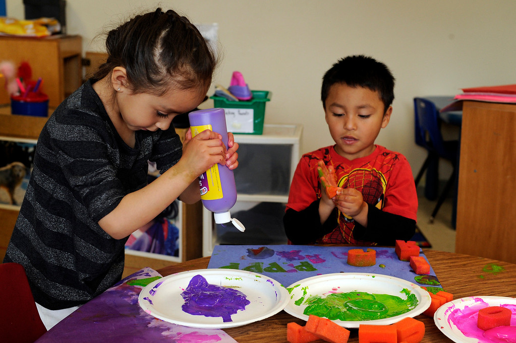 Description of . DENVER, CO - APRIL 3: Sophia S., 4, and Pablo P., 4, paint during activity time in their preschool class at the Children's Outreach Project on April 3, 2014, in Denver, Colorado. The school is a nonprofit that provides therapy, education and daycare to children between 2-6 years old who have developmental delays like moderate Down syndrome and speech impediments. (Photo by Anya Semenoff/The Denver Post)