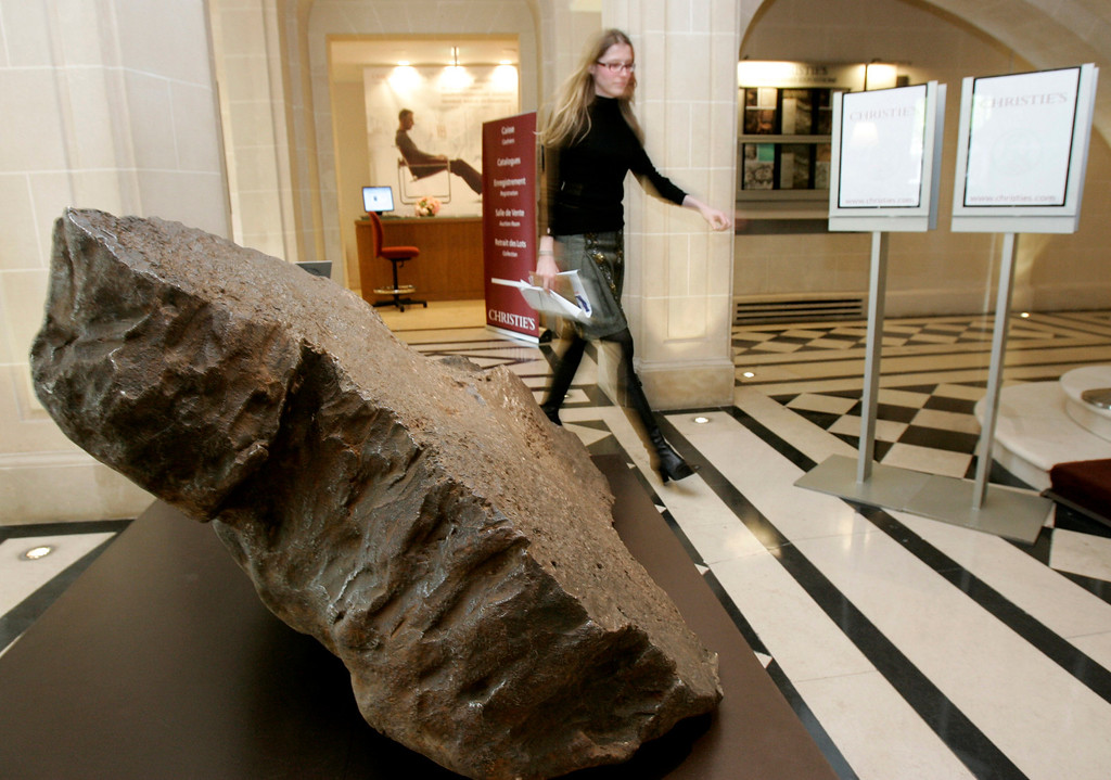Description of . A woman walks past the Seymchan meteorite at Christie's auction house in Paris, Wednesday, April 2, 2008. The 2.7-ton meteorite discovered in eastern Russia in 1967 will go on auction on April 16. (AP Photo/Francois Mori)
