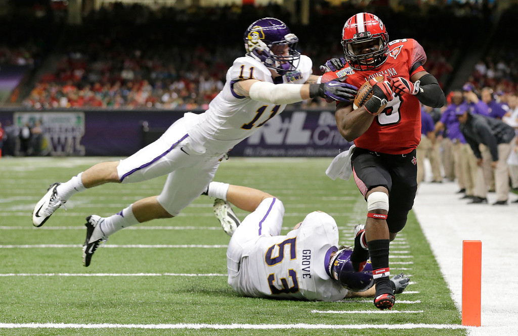 Description of . Louisiana-Lafayette wide receiver Harry Peoples (9) scores a touchdown as East Carolina defensive back Damon Magazu (11) and linebacker Jeremy Grove (53) defend in the first half of the New Orleans Bowl, an NCAA college football game in New Orleans, Saturday, Dec. 22, 2012. (AP Photo/Dave Martin)