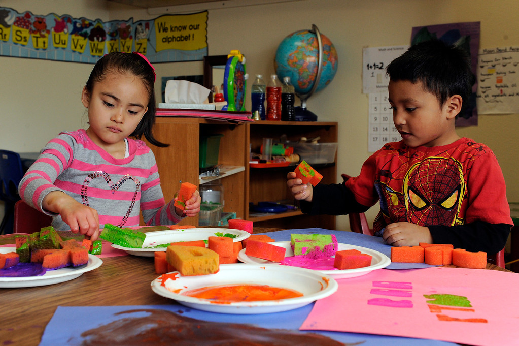 Description of . DENVER, CO - APRIL 3: Heidy P., 5, and Pablo P., 4, paint during activity time in their preschool class at the Children's Outreach Project on April 3, 2014, in Denver, Colorado. The school is a nonprofit that provides therapy, education and daycare to children between 2-6 years old who have developmental delays like moderate Down syndrome and speech impediments. (Photo by Anya Semenoff/The Denver Post)