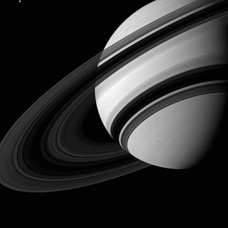 Description of . The moon Tethys (in the upper left of the image) is seen next to Saturn in this NASA handout image from the Cassini spacecraft taken August 19, 2012 and released December 3, 2012.  Saturn's rings appear to dwarf Tethys (660 miles, or 1,062 kilometers across) although scientists believe the moon to be many times more massive than the entire ring system combined. The view was acquired at a distance of approximately 1.5 million miles (2.4 million kilometers) from Saturn. REUTERS/NASA/JPL-Caltech/Space Science Institute/Handout
