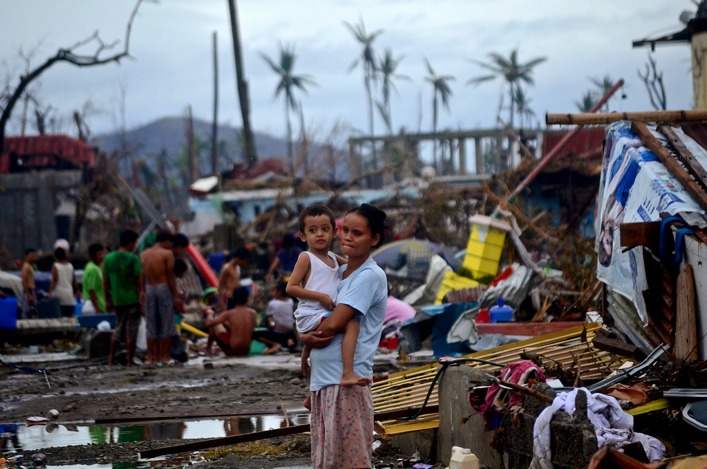 Description of . A woman holds a child surrounded by debris in an area devastated by Typhoon Haiyan on November 12, 2013 in Leyte, Philippines.   (Photo by Dondi Tawatao/Getty Images)