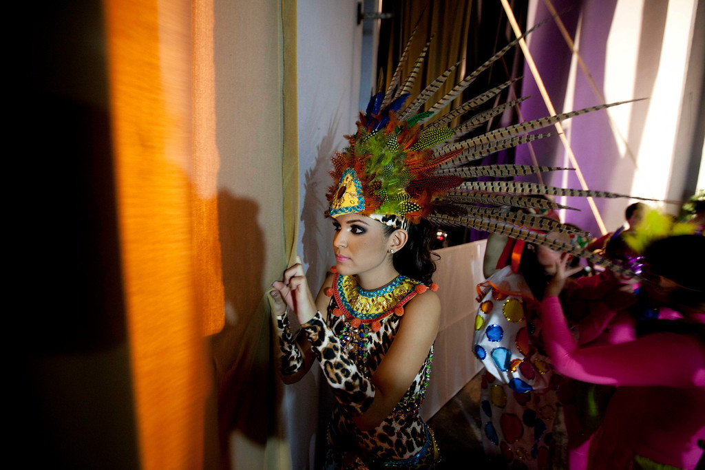 Description of . In this Jan. 26, 2013 photo, beauty contestant Donaji Lopez peers from backstage as she watches other contestants perform during the