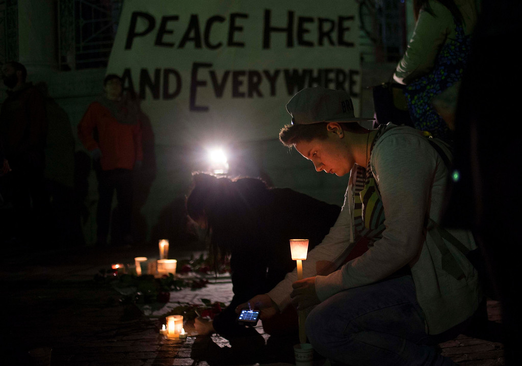 . Samantha Lacovara takes pictures of a banner mourners were signing during a candlelight vigil for bomb victims a day after two explosions hit the Boston Marathon, in Boston, Massachusetts April 16, 2013. The twin blasts on Monday killed three people including an 8-year-old boy and injured 176 others, some of whom were maimed by bombs packed with ball bearings and nails. REUTERS/Adrees Latif