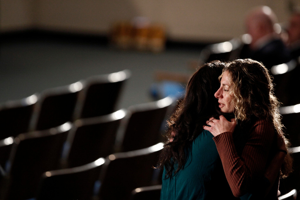 Description of . Mourners embrace before a memorial service for victims of the shooting at Sandy Hook Elementary School in the auditorium of Newtown High School in Newtown, Conn., Dec. 16, 2012. President Barack Obama will speak at the memorial and meet privately with families and first responders. (Luke Sharrett/The New York Times)