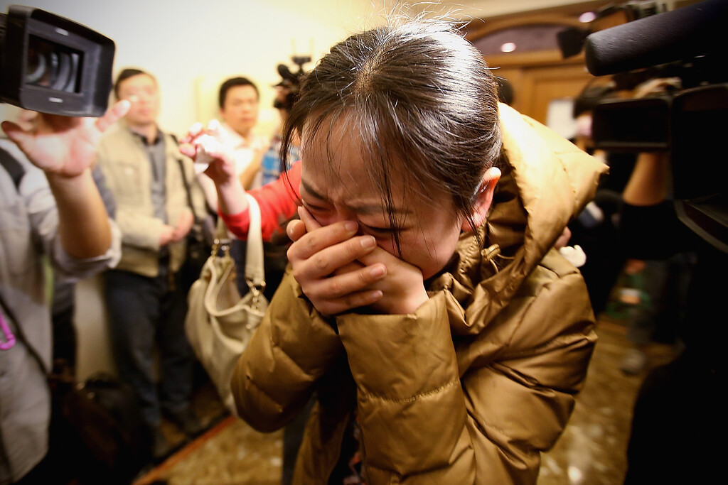 Description of . A relative of a passenger onboard Malaysia Airlines flight MH370 cries out at a local hotel where families are gathered on March 9, 2014 in Beijing, China. Malaysia Airline Flight MH370 from Kuala Lumpur to Beijing and carrying 239 onboard was reported missing after the crew failed to check in as scheduled while flying over the sea between Malaysia and Ho Chi Minh City in Vietnam, according to published reports.  (Photo by Feng Li/Getty Images)