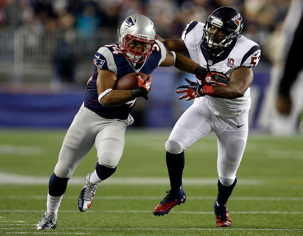 Description of . New England Patriots running back Shane Vereen, left, evades a tackle by Houston Texans linebacker Bradie James during the first half of an AFC divisional playoff NFL football game in Foxborough, Mass., Sunday, Jan. 13, 2013. (AP Photo/Elise Amendola)