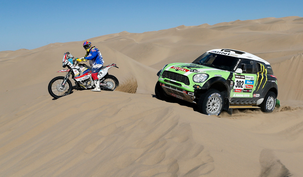 Description of . Stephane Peterhanzel and Jean Paul Cottret, both of France, right, overtakes Yamaha rider Gustavo Querales Malave of Venezuela, left, during the 4nd stage of the 2013 Dakar Rally from Nazca to Arequipa, Peru, Tuesday, Jan. 8, 2013. The race finishes in Santiago, Chile, on Jan. 20. (AP Photo/Victor R. Caivano)