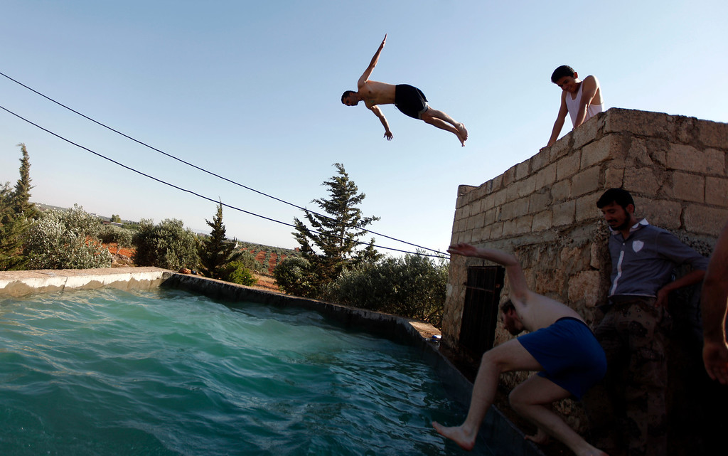Description of . FILE - Free Syrian Army fighters swim in a pool on the outskirts of Aleppo, Syria, Tuesday, June 12, 2012. (AP Photo/File)