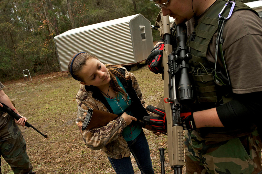 ". A member of the North Florida Survival Group shows the daughter of another member how to operate the magazine release of an SKS rifle during a field training exercise in Old Town, Florida, December 8, 2012.  The group trains children and adults alike to handle weapons and survive in the wild. The group passionately supports the right of U.S. citizens to bear arms and its website states that it aims to teach ""patriots to survive in order to protect and defend our Constitution against all enemy threats\"". Picture taken December 8, 2013.   REUTERS/Brian Blanco"