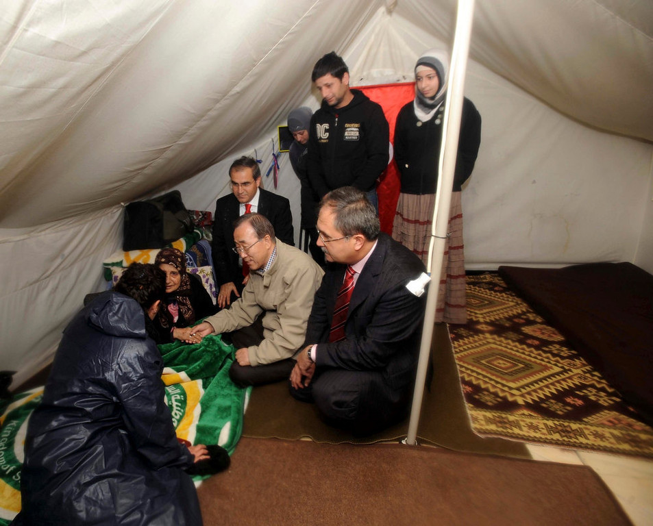 Description of . U.N. Secretary-General Ban Ki-moon (squatting C) chats with a Syrian refugee woman during his visit to a camp in the Turkish town of Islahiye, Gaziantep province December 7, 2012. Ban said on Friday he was not aware of any confirmed reports that Syrian President Bashar al-Assad was preparing to use chemical weapons but that if he did so it would be an