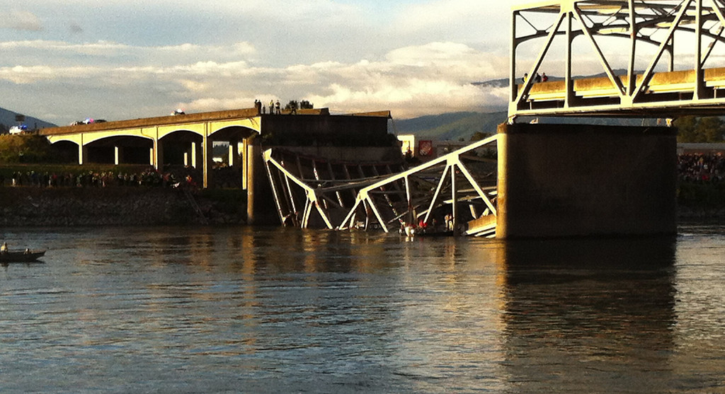 Description of . People look on after the Interstate 5 bridge collapsed over the Skagit River in Mount Vernon, Wash., Thursday, May 23, 2013. (AP Photo/The Seattle Times, Rick Lund)