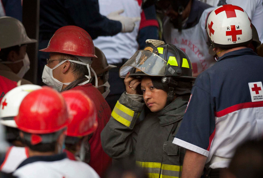 Description of . Rescue workers and firefighters gather  as emergency responders search for trapped survivors at the site on an explosion in a building at Mexico's state-owned oil company PEMEX complex, in Mexico City.  (AP Photo/Eduardo Verdugo)