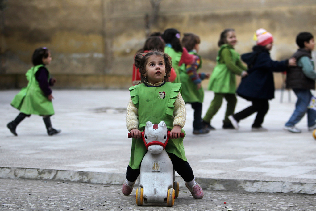 Description of . A girl looks up to the sky after hearing the sound of shelling as she sits on a toy pony in the playground of Al-Tawheed school in Aleppo January 1, 2013. REUTERS/Muzaffar Salman