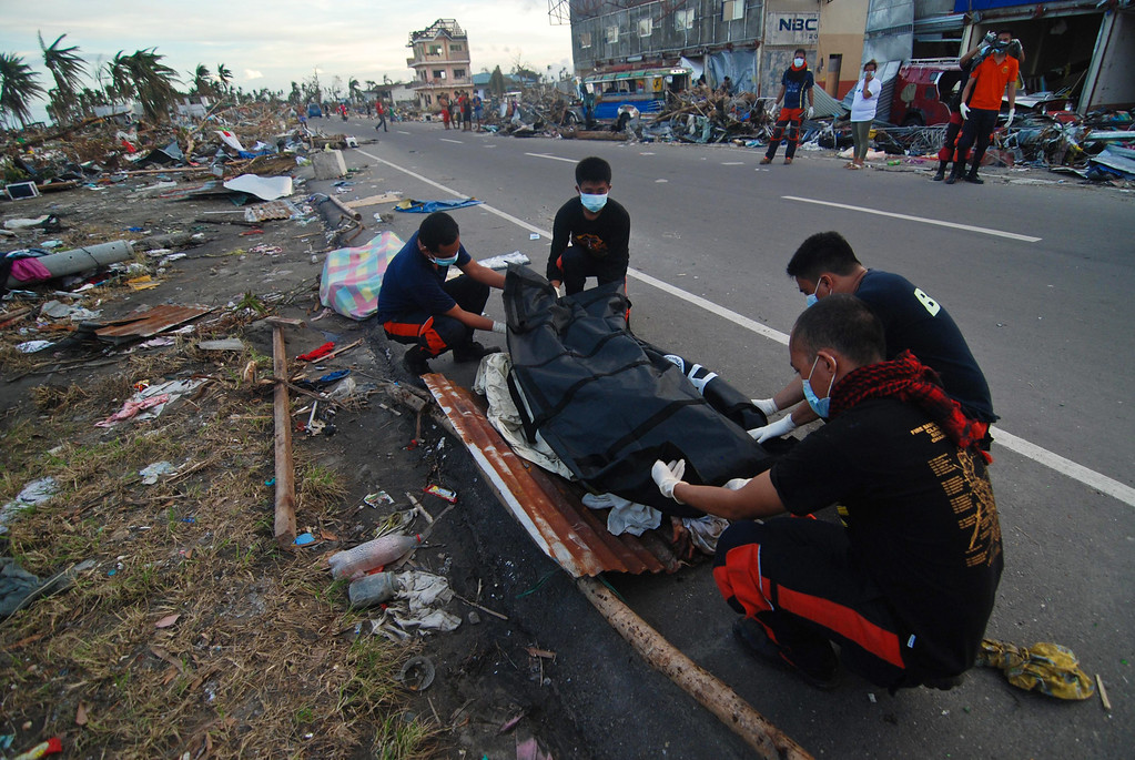 Description of . Members of the fire department retrieve bodies from the rubble in Tacloban City on November 14, 2013 in Leyte, Philippines. Typhoon Haiyan which ripped through Philippines over the weekend has been described as on of the most powerful typhoons ever to hit land, leaving thousands dead and hundreds of thousands homeless.  (Photo by Dondi Tawatao/Getty Images)