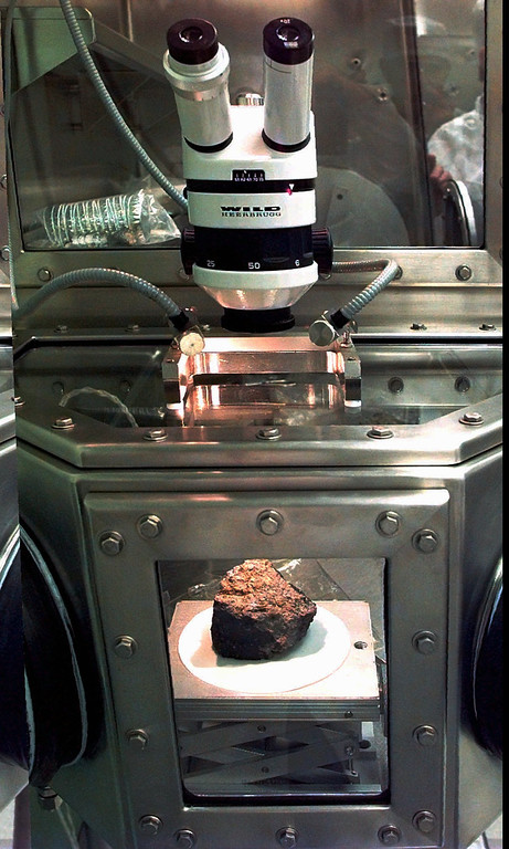 Description of . The meteorite labeled ALH84001 sits under a microscope at a Johnson Space Center lab in Houston,in this Aug. 7, 1996 file photo. Researchers at NASA and three universities claimed to have found in the rock from Mars organic compounds they said were deposited by primitive life forms before the meteorite was blasted into space and sent on a 15 million-year voyage to Earth. (AP Photo/David J. Phillip)