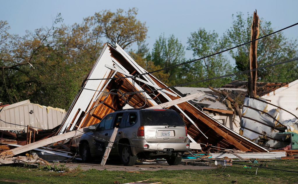 Description of . An SUV is covered by debris from a tornado in Baxter Springs, Kan., Monday, April 28, 2014. Sunday's tornado damaged dozens of buildings and injured at least 25 people. (AP Photo/Orlin Wagner)