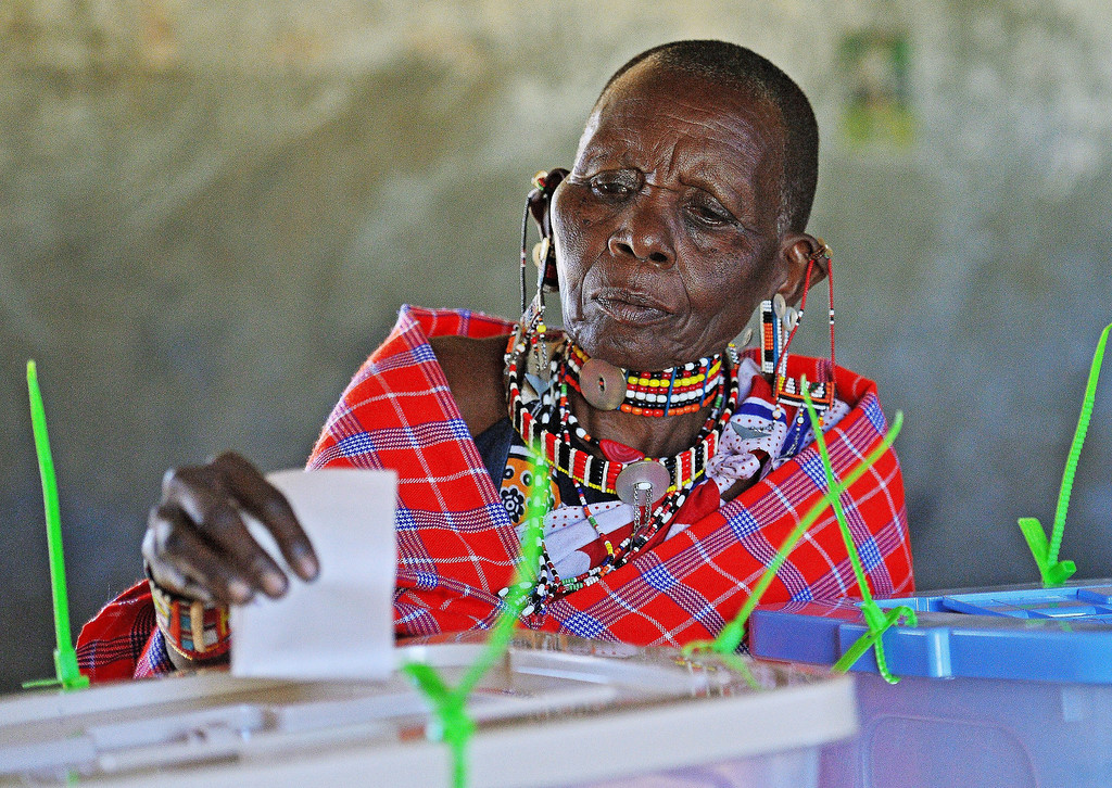 Description of . An elederly Maasai woman is watched over by an IEBC official as she casts her vote in Ilngarooj, Kajiado County, Maasailand, on March 4, 2013 during the nationwide elections. Long lines of Kenyans queued from way before dawn to vote Monday in the first election since the violence-wracked polls five years ago, with a deadly police ambush hours before polling started marring the key ballot. The tense elections are seen as a crucial test for Kenya, with leaders vowing to avoid a repeat of the bloody 2007-8 post-poll violence in which over 1,100 people were killed and observers repeatedly warning of the risk of renewed conflict.    CARL DE SOUZA/AFP/Getty Images