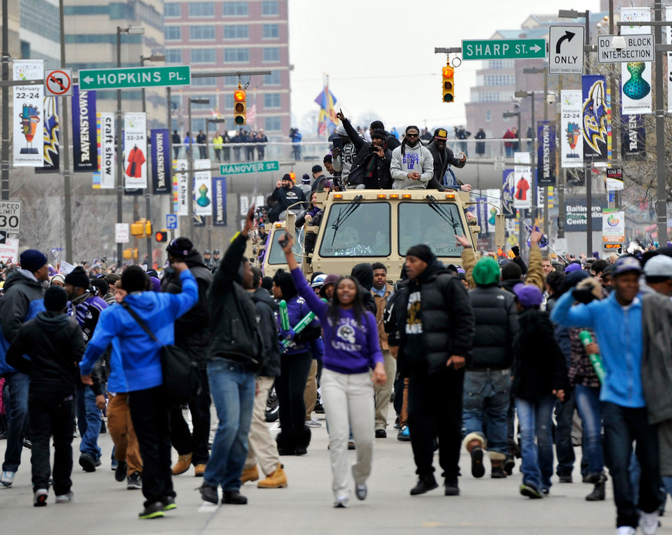 Description of . Baltimore Ravens fans break through barriers and walk with players during a victory parade Tuesday, Feb. 5, 2013, in Baltimore. The Ravens defeated the San Francisco 49ers in NFL football's Super Bowl XLVII 34-31 on Sunday. (AP Photo/Gail Burton)