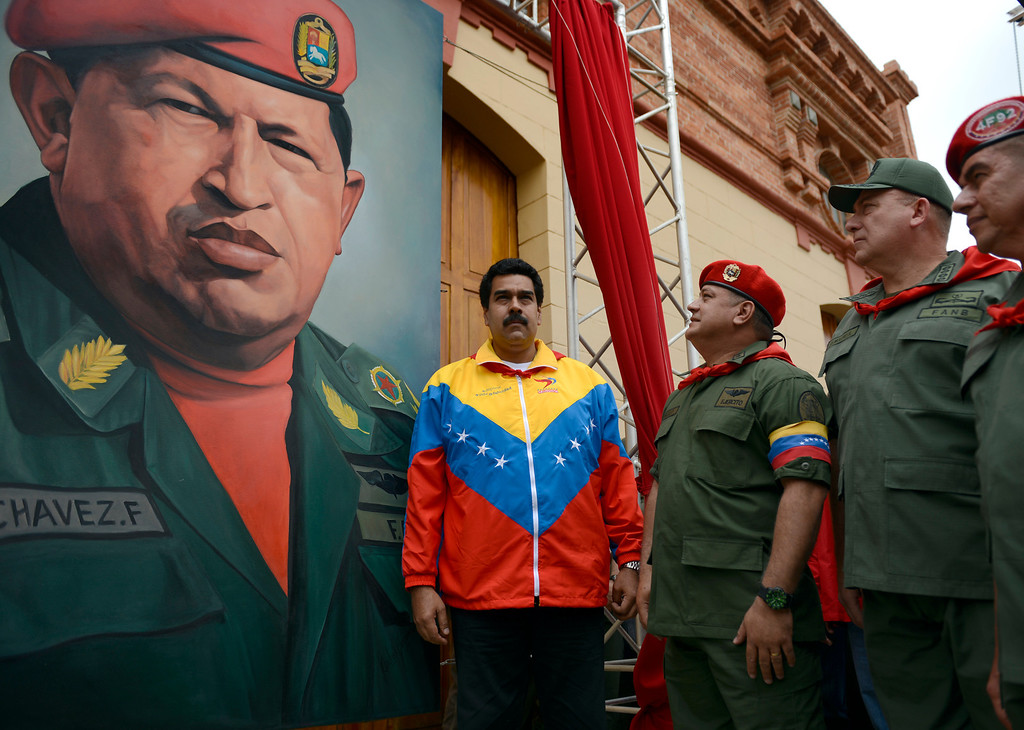 Description of . (L to R) Venezuelan Vice President Nicolas Maduro, the president of the National Assembly, Diosdado Cabello and Venezuelan Minister of Defense Diego Molero Bellavia, stand next to a huge portrait of Venezuelan President Hugo Chavez during the conmemoration of the 1992 failed coup led by Chavez, who was an army lieutenant colonel, against then president Carlos Andres Perez, in Caracas, on February 4, 2013. Ailing President Hugo Chavez, who had cancer surgery in December, is doing much better and recovering, Cuban leader Fidel Castro said in remarks published Monday.  JUAN BARRETO/AFP/Getty Images