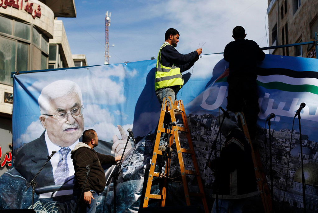 Description of . Labourers put up a banner depicting Palestinian President Mahmoud Abbas before a rally in the West Bank city of Ramallah, supporting the resolution that would change the Palestinian Authority's United Nations observer status from