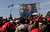 A screen showing a video image of Venezuela's President Hugo Chavez plays in front of the site where Chavez's funeral ceremony will take place as people gather outside the military academy in Caracas, Venezuela, Friday, March 8, 2013. (AP Photo/Rodrigo Abd)
