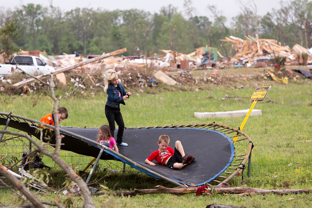 Description of . Children play on a mangled trampoline near the home of their grandparents, Gayla and Gary Evatt who lived off Naylor Road in Vilonia, Ark., Monday, April 28, 2014 after a tornado struck the town late Sunday. The Evatts said the trampoline and their home, survived the tornado in 2011, but this year both weren't so lucky.  (AP Photo/Karen E. Segrave)