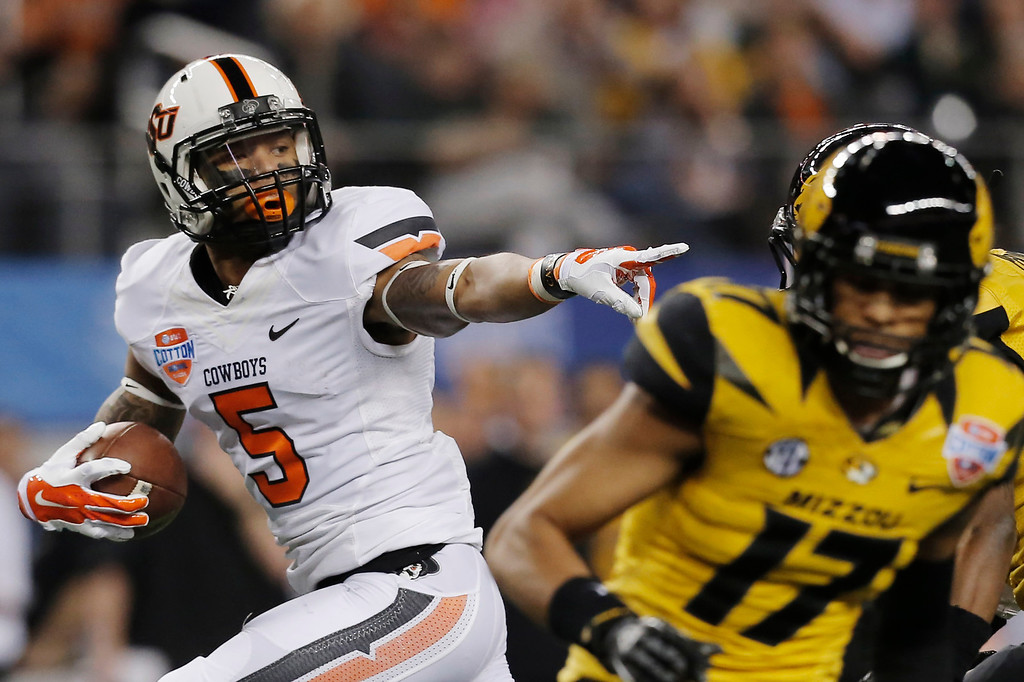 Description of . Oklahoma State wide receiver Josh Stewart (5) gestures on his way in for a touchdown against Oklahoma State during the first half of the Cotton Bowl NCAA college football game on Friday, Jan. 3, 2014, in Arlington, Texas. (AP Photo/Brandon Wade)