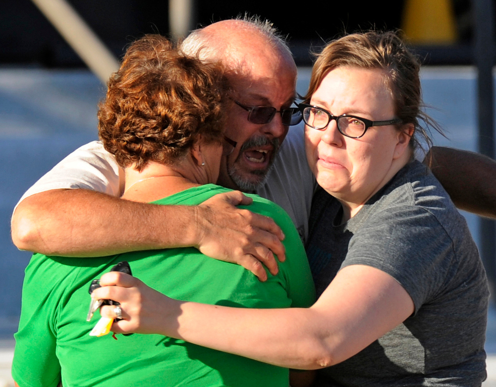 Description of . Tom Sullivan, center, hugs his wife Terry, left, and daughter Megan outside Gateway High School, Friday, July 20, 2012, in Aurora. Sullivan was still missing his son, Alex, after a gunman opened fire at a crowded movie theater. Alex would later be identified as one of twelve people fatally shot in the massacre. RJ Sangosti, The Denver Post