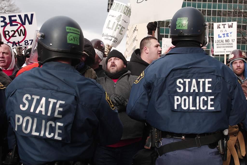 Description of . Michigan State Police in riot gear push have a stand-off with protestors who linked arms and blocked a street during a rally at the Michigan State Capitol to protest a vote on Right-to-Work legislation December 11, 2012 in Lansing, Michigan. Republicans control the Michigan House of Representatives, and Michigan Gov. Rick Snyder has said he will sign the bill if it is passed. The new law would make requiring financial support of a union as a condition of employment illegal. (Photo by Bill Pugliano/Getty Images)