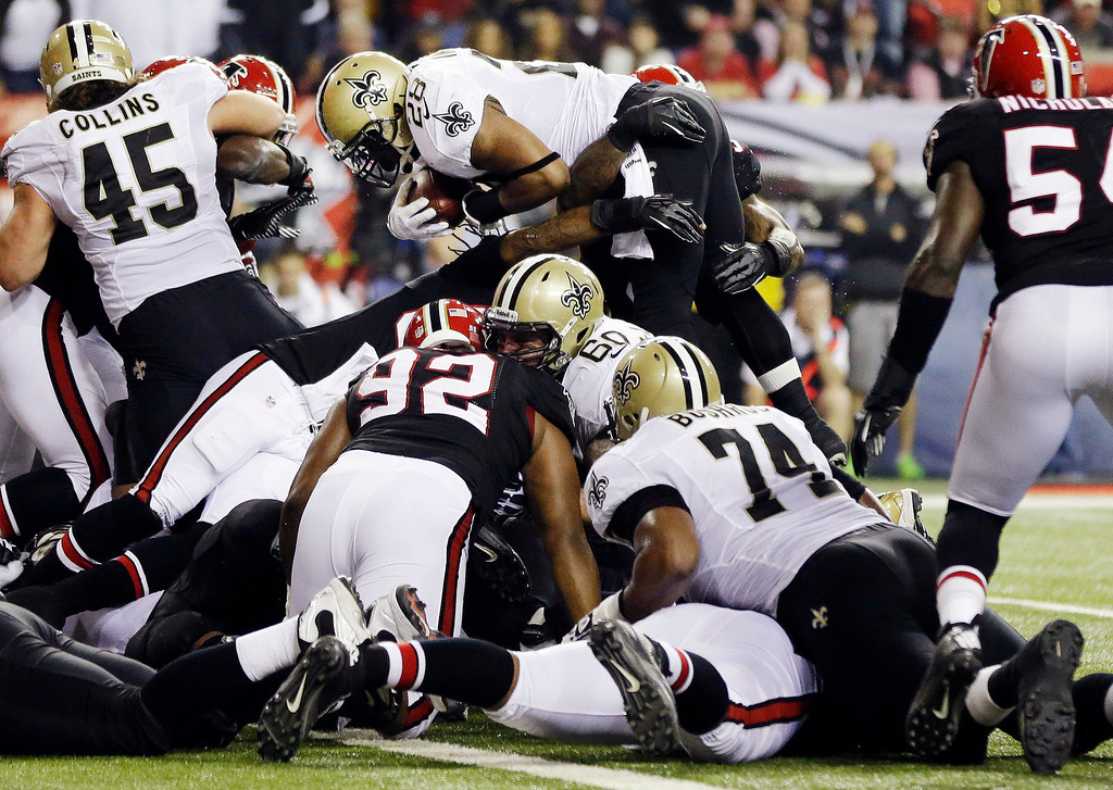 Description of . New Orleans Saints running back Mark Ingram (28) goes over the top to score a touchdown during the first half of an NFL football game against the Atlanta Falcons, Thursday, Nov. 29, 2012, in Atlanta. (AP Photo/David Goldman)