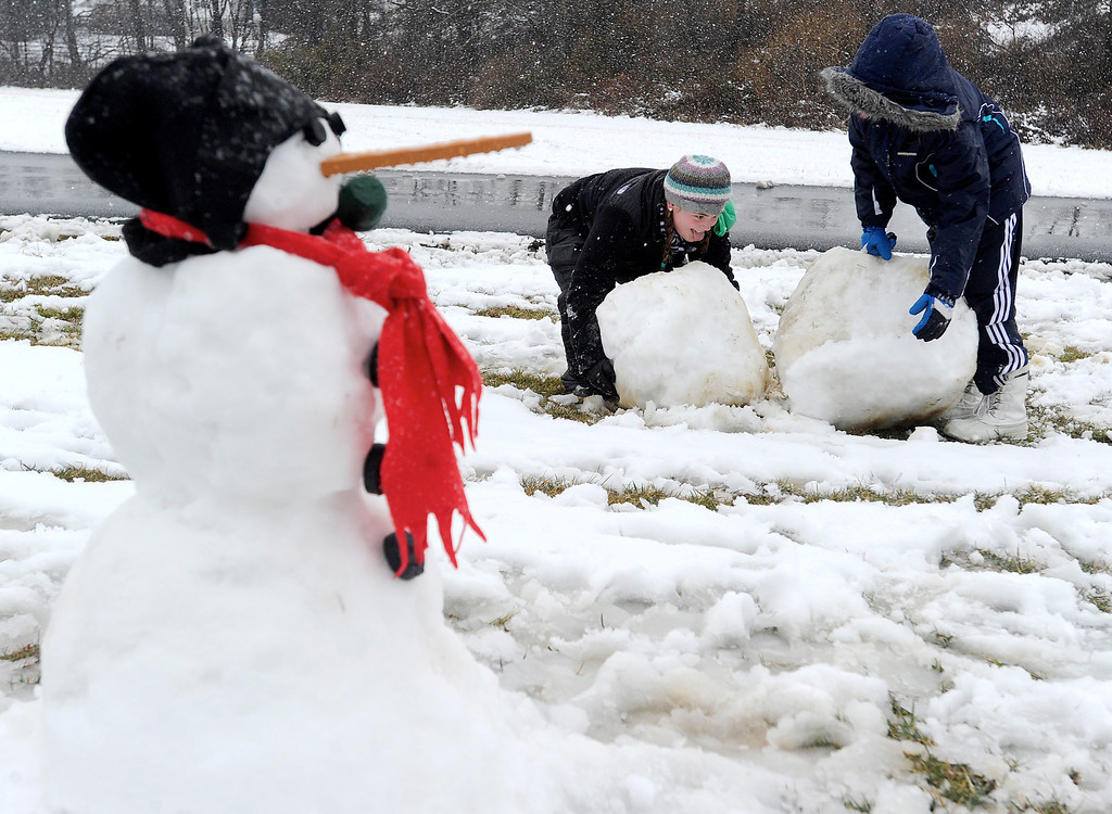 Description of . Marli Baldwin, 12, left, and Alina Nowosielski, 11, build a snowman in Westminster, Md. Wednesday, March 6, 2013.  Carroll County Public Schools were closed Wednesday. (AP Photo/Carroll County Times, Dave Munch)