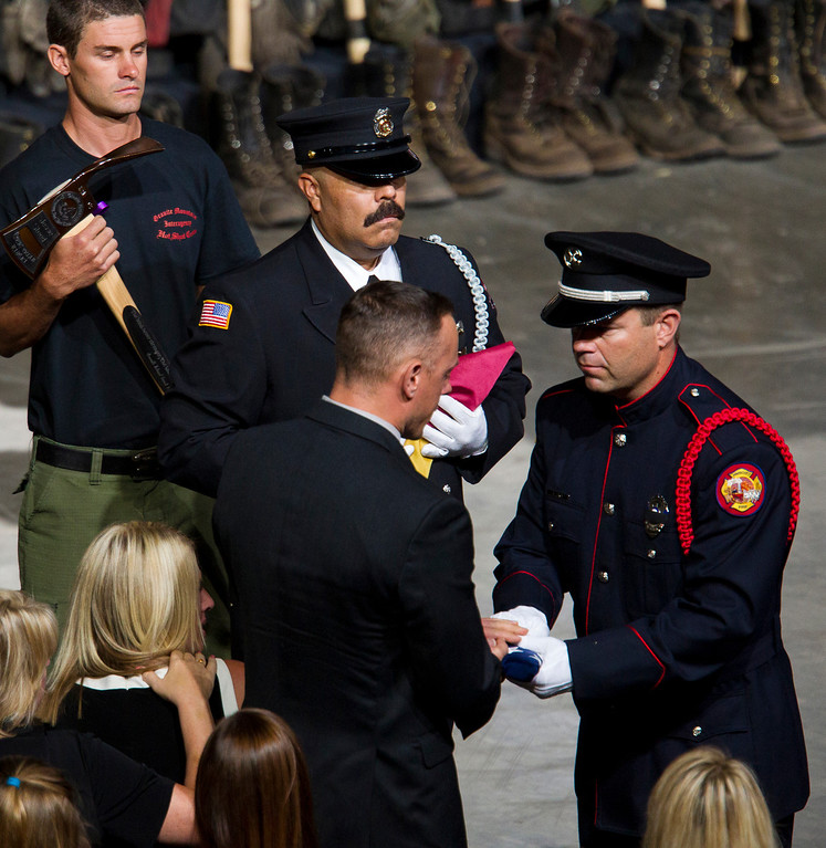 Description of . A flag is presented to the family of fallen firefighter Jesse Steed during a memorial service for the 19 fallen firefighters at Tim's Toyota Center in Prescott Valley, Ariz. on Tuesday, July 9, 2013.   (AP Photo/The Arizona Republic, Michael Chow, Pool)