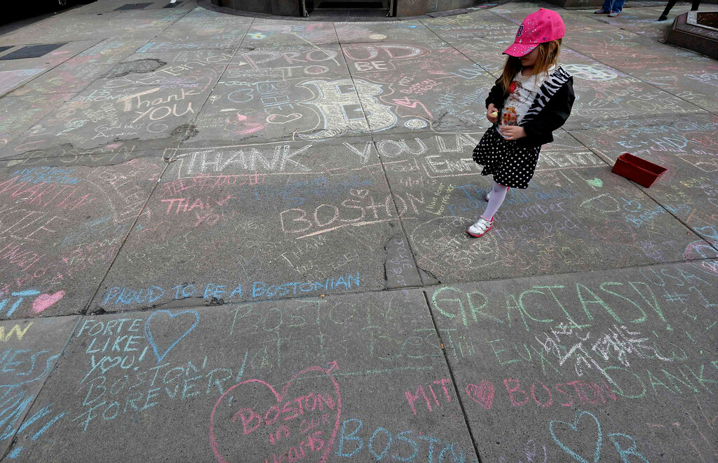 Description of . Jane Cosmas, 4-years-old, of Somerville, Massachusetts, walks amidst hundreds of chalk messages written by passersby about the Boston Marathon bombings on Newbury Street near the scene of the blasts in Boston, Massachusetts, April 20, 2013. REUTERS/Jim Bourg