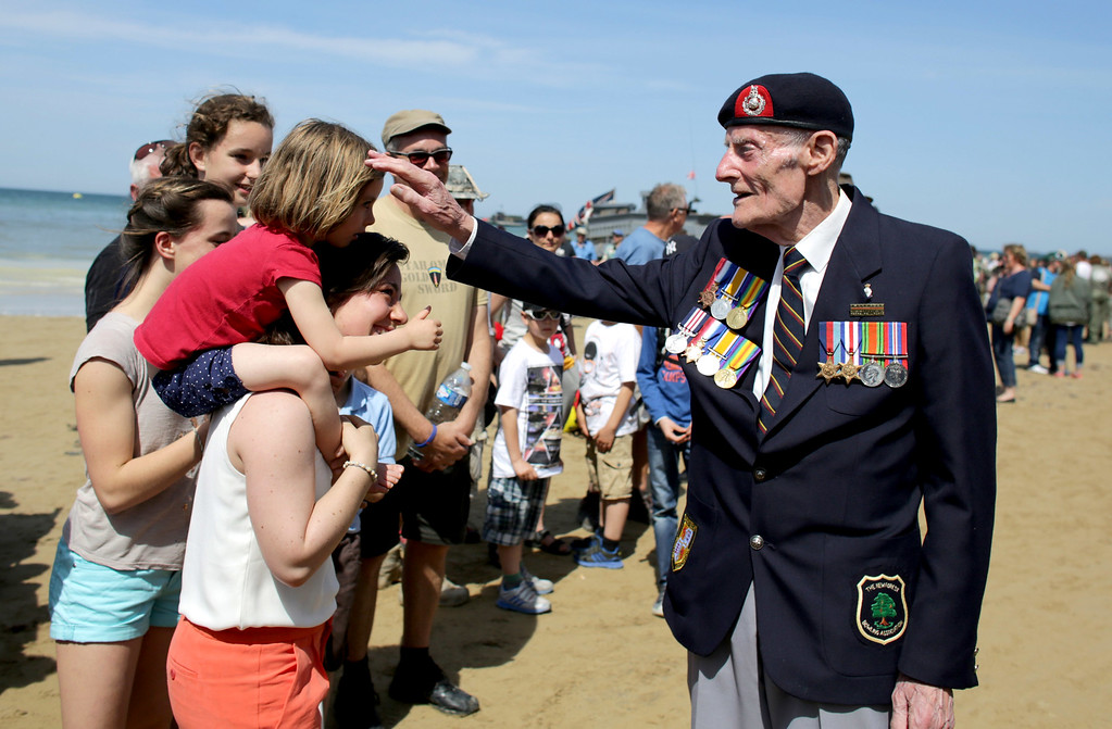 Description of . Joseph Kellsey, 91, who was in the Royal Marines on Sword Beach on D-Day greets people he walks on the beach at Arrowmanches-Les-Bains during D-Day 70 Commemorations on June 6, 2014 near Bayeux, France.  (Photo by Matt Cardy/Getty Images)