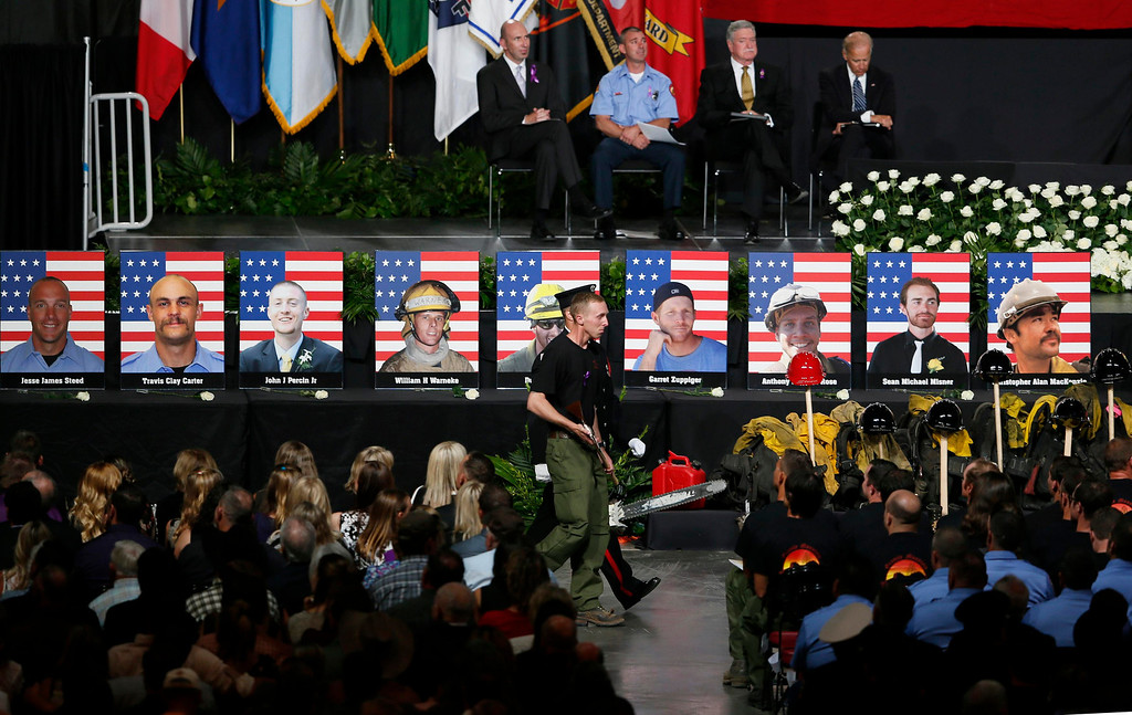 Description of . Surviving Hotshot crew member Brendan McDonough walks back to his seat at a memorial service after presenting the U.S. flag to families of the fallen members of the Granite Mountain Hotshots, in Prescott Valley, Arizona July 9, 2013.REUTERS/Lucy Nicholson