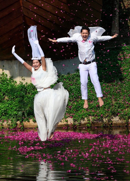 Description of . Thai groom Prasit Rangsiyawong (R), 29, and his bride Varuttaon Rangsiyawong, 27, jump in a pond during a wedding ceremony ahead of Valentine's Day in Prachin Buri province, east of Bangkok February 13, 2013. Three Thai couples took part in the wedding ceremony arranged by a Thai resort, aimed to strengthen the relationships of the couples by doing fun activities.  REUTERS/Kerek Wongsa