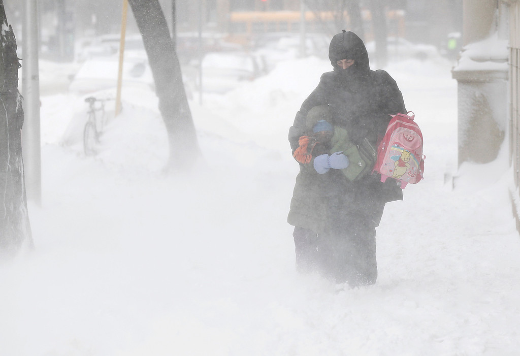 Description of . Commuters bundle up together as they walk against blowing snow Wednesday, Feb. 5, 2014, in Chicago. Heavy, blowing snow is moving across much of Illinois as the state gets pelted by the latest round of winter weather. (AP Photo/Kiichiro Sato)